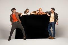 Группа в составе друзья показывая пустую черную доску Стоковое Изображение RF