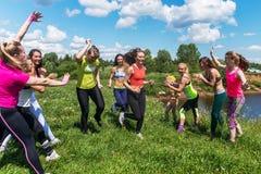 Группа в составе excited женщины пересекая finshline марафон бежать на травянистой земле в парке Стоковая Фотография RF