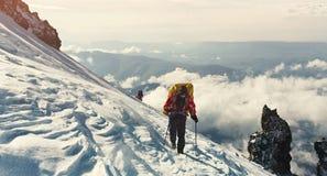 Группа в составе hikers в горе Подъем к верхней части альпинисты с рюкзаками на следе стоковые изображения rf