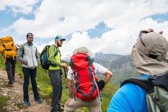 Группа в составе hikers с рюкзаками и отслеживать вставляет остатки и стоит в горах слушая к их гиду Стоковое фото RF