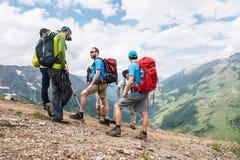 Группа в составе hikers с рюкзаками и отслеживать вставляет остатки и стоит в горах слушая к их гиду Стоковые Изображения RF