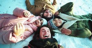 Группа в составе multi этнические друзья наслаждаясь временем совместно в зимнем времени они кладя вниз на пол делают круг видеоматериал