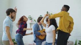 Группа в составе multi этнические друзья танцуя пока молодой человек играя гитару и имея домашнюю партию внутри помещения видеоматериал
