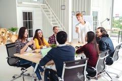 Группа в составе multiracial молодая творческая команда говоря, смеясь над и коллективно обсуждать в встрече на современной конце стоковая фотография rf