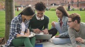 Группа в составе multiracial студенты колледжа используя ноутбук акции видеоматериалы
