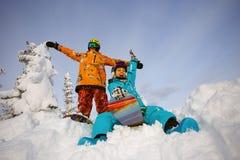 Группа в составе snowboarders друзей имея потеху на верхней части горы Стоковое фото RF
