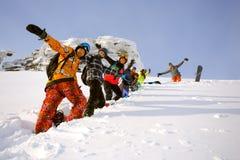 Группа в составе snowboarders друзей имея потеху на верхней части горы Стоковая Фотография