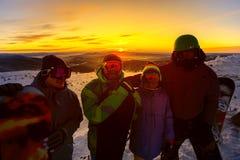 Группа в составе snowboarders друзей имея потеху на верхней части горы Стоковые Изображения RF