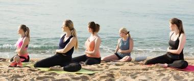 Группа в составе sporty девушки практикуя различные положения йоги во время t стоковые фото