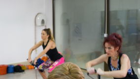 Группа в составе sporty женщины разрабатывая на фитнес-клубе видеоматериал