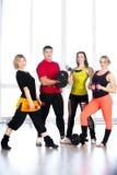 Группа в составе sporty люди держа гантели в спортзале Стоковые Изображения