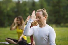 Группа в составе yogis в природе выполняет дышая тренировки Стоковые Фото