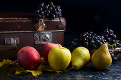 Группа голубых виноградин и зрелых плодоовощей на темной мраморной предпосылке Стоковые Фото