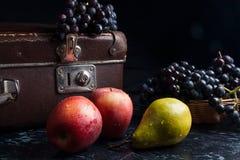 Группа голубых виноградин и зрелых плодоовощей на темной мраморной предпосылке Стоковое Фото