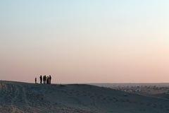 Группа и ребенок людей Silhoutted на Песк-дюнах на сумраке Стоковое Фото