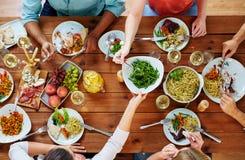 Группа людей есть на таблице с едой Стоковые Фото