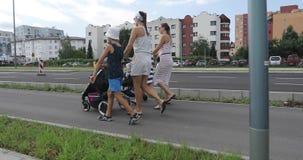 Группа людей идет вдоль дороги в городе акции видеоматериалы
