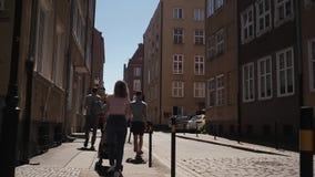 Группа людей идет идти вниз по улице от задней части акции видеоматериалы