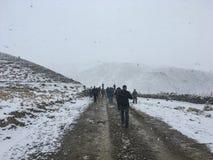 Группа людей идя на грязную улицу в снеге Стоковые Фотографии RF