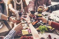 Группа людей имея единение еды обедая провозглашающ тост стекла Стоковое Изображение RF