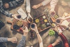 Группа людей имея единение еды обедая провозглашающ тост стекла Стоковое Фото