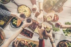 Группа людей имея единение еды обедая провозглашающ тост стекла Стоковое Изображение