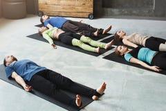Группа людей на занятиях йогой, лежа на поле после exerices стоковая фотография