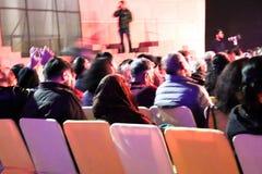 Группа людей сидя на стульях и наблюдая представлении этапа в реальном маштабе времени стоковое фото rf