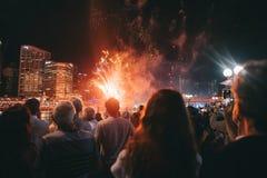 Группа людей собранная вокруг на фестивале наслаждаясь яркими фейерверками стоковые изображения rf