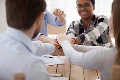 Группа людей штабелируя руки сидя в офисе совместно стоковые фото