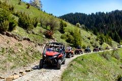 Группа путешествия путешествует на ATVs и UTVs на горах Стоковая Фотография RF