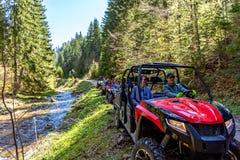 Группа путешествия путешествует на ATVs и UTVs на горах Стоковое Фото