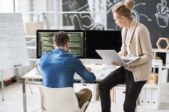 Группа разработчиков обсуждая состав команд вычислительной машины стоковое изображение