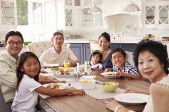Группа семьи из нескольких поколений есть еду дома совместно Стоковые Изображения