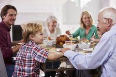 Группа семьи из нескольких поколений сидит вокруг таблицы есть еду дома Стоковое фото RF