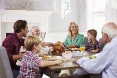 Группа семьи из нескольких поколений сидит вокруг таблицы есть еду дома Стоковая Фотография