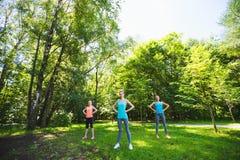 Группа фитнеса делая йогу в парке на солнечный день Стоковые Изображения RF