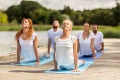 Группа людей делая йогу работает outdoors Стоковое Изображение