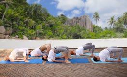 Группа людей делая тренировки йоги над пляжем Стоковое Изображение