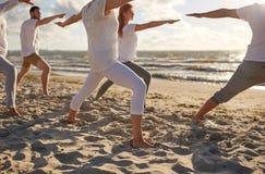 Группа людей делая тренировки йоги на пляже Стоковые Фото