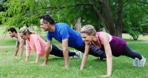 Группа людей делая тренировку нажима-вверх совместно в парке видеоматериал
