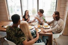 Группа людей имея обедающий и говоря на кухне Стоковые Фотографии RF