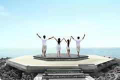 Группа людей на повышении скалы вручает совместно стоковое изображение