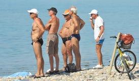 Группа людей около моря для того чтобы противодействовать слишком горячее лето Стоковая Фотография RF
