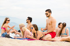 Группа людей отдыхая на пляже Стоковые Изображения