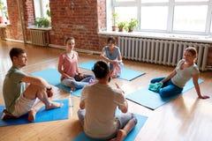 Группа людей отдыхая на циновках йоги на студии Стоковые Изображения