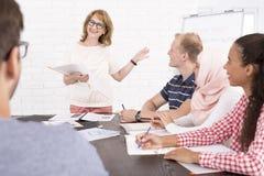 Группа людей сидя на столе и смотря диктора Стоковые Фото