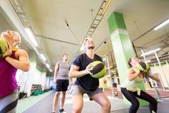 Группа людей с тренировкой шарика медицины в спортзале Стоковая Фотография RF