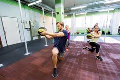 Группа людей с тренировкой шарика медицины в спортзале Стоковая Фотография