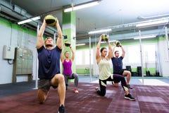 Группа людей с тренировкой шарика медицины в спортзале Стоковые Фотографии RF